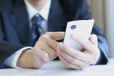 スマートフォンで不動産の情報を見ている人のイメージ